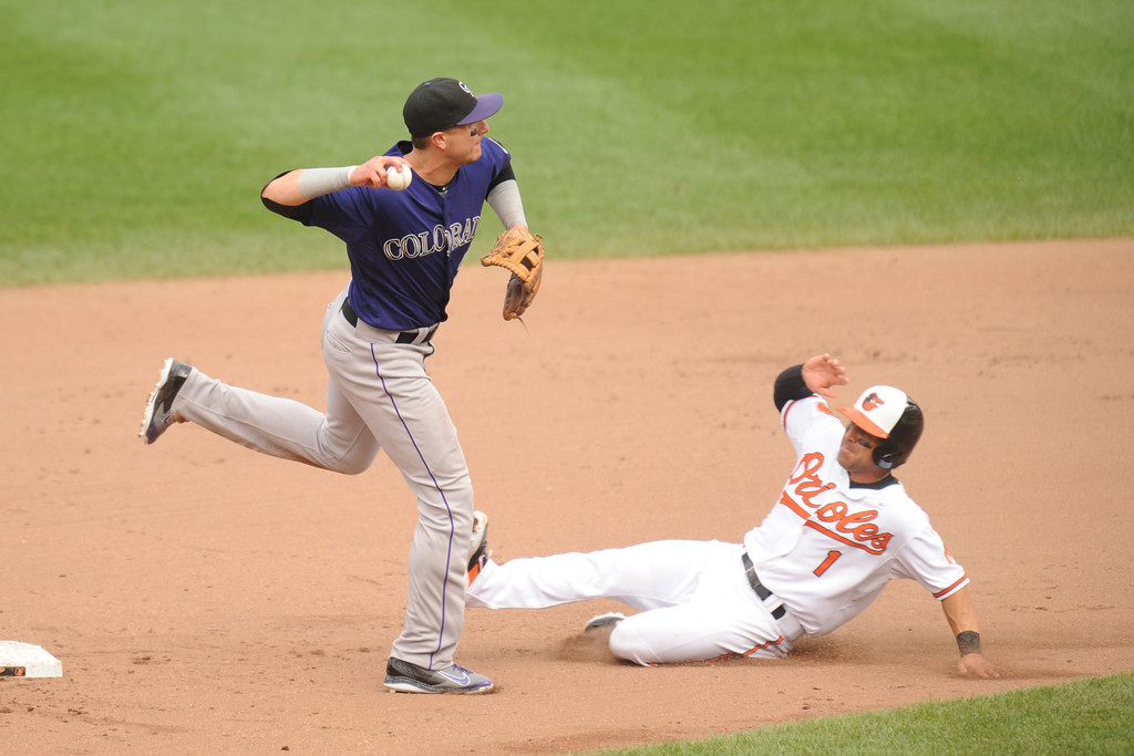 . Troy Tulowitzki #2 of the Colorado Rockies forces out Brian Roberts #1 of the Baltimore Orioles at second base in the seventh inning during a baseball game on August 18, 2013 at Oriole Park at Camden Yards in Baltimore, Maryland.  The Oriole swon 7-2.  (Photo by Mitchell Layton/Getty Images)