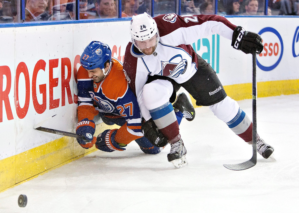 . Colorado Avalanche\'s Marc-Andre Cliche (24) checks Edmonton Oilers\' Boyd Gordon (27) during first period NHL hockey action in Edmonton, Alta., on Tuesday April 8, 2014. (AP Photo/The Canadian Press, Jason Franson)