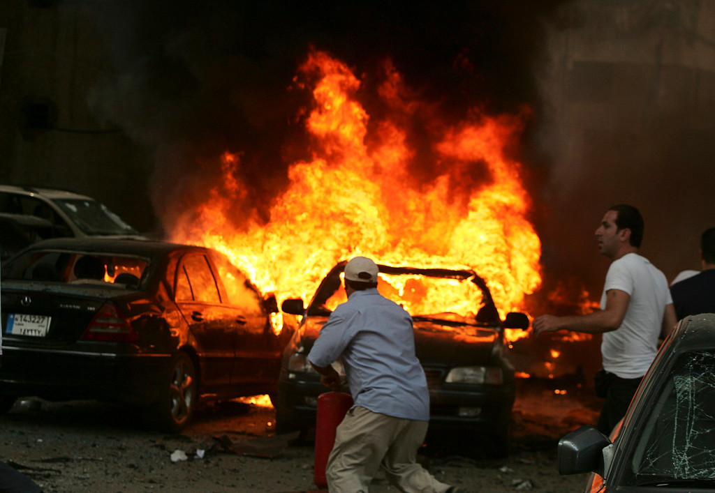 . Men try to extinguish fire from burning cars at the site of an explosion, in Beirut\'s southern suburbs, July 9, 2013. Several people were killed or wounded when a car bomb hit Beirut\'s southern suburbs on Tuesday, a stronghold for the Lebanese Shi\'ite Hezbollah militant group that has been fighting in Syria\'s civil war, medics said. REUTERS/Issam Kobeisy