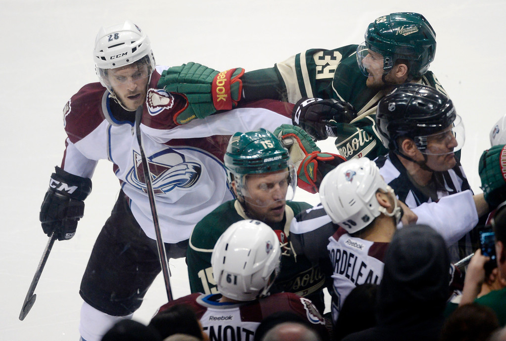 . Colorado center Paul Carey (28) and Minnesota defenseman Nate Prosser (39) joined a scrum in the first period. The Minnesota Wild defeated the Colorado Avalanche 1-0 in overtime at the Xcel Energy Center in St. Paul Monday night, April 21, 2014. (Photo by Karl Gehring/The Denver Post)