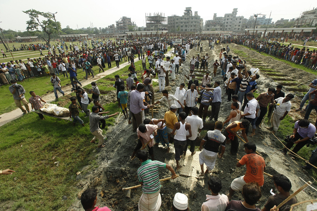 . Bangladeshis bury the remains of garment workers killed in the garment factory collapse at a graveyard in Dhaka on May 1, 2013.  AFP PHOTO/STRSTRDEL/AFP/Getty Images