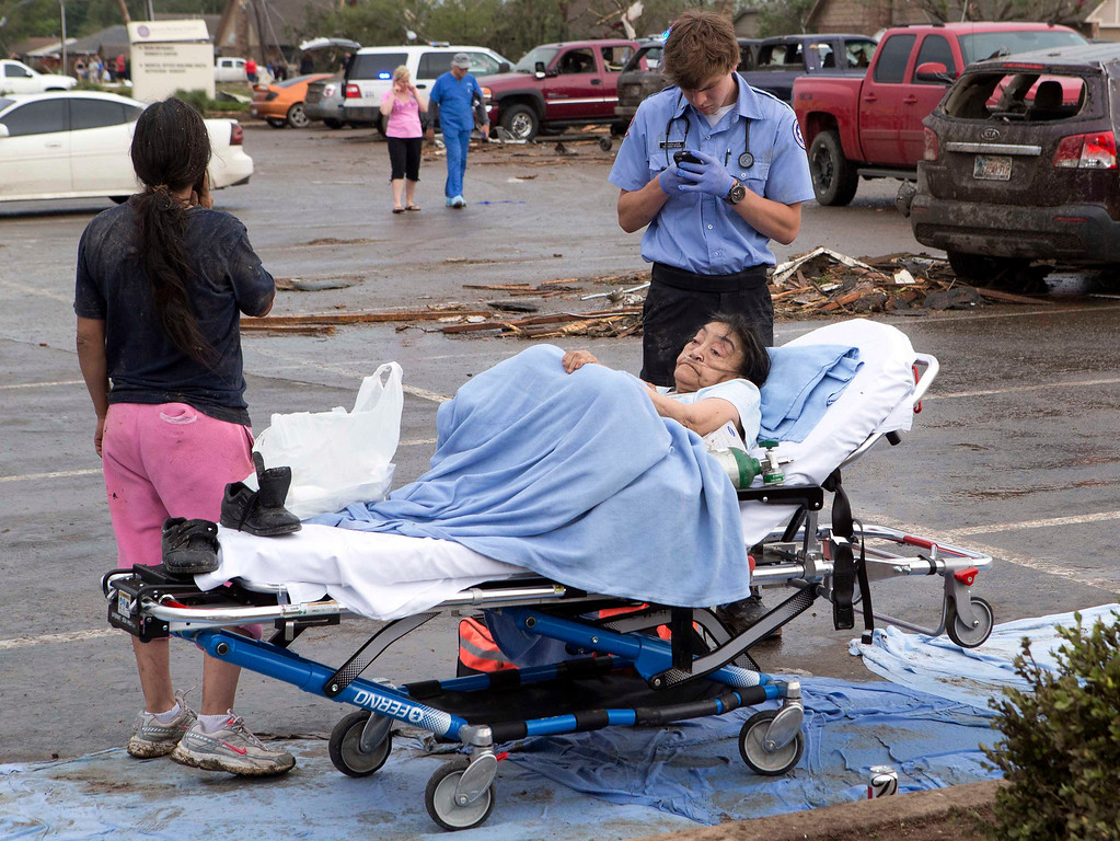 . A woman is tended to by a Emergency Medical Technician after a huge tornado struck Moore, Oklahoma, near Oklahoma City, May 20, 2013. A massive tornado tore through the Oklahoma City suburb of Moore on Monday, killing at least 51 people as winds of up to 200 miles per hour (320 kph) flattened entire tracts of homes, two schools and a hospital, leaving a wake of tangled wreckage.    REUTERS/Richard Rowe