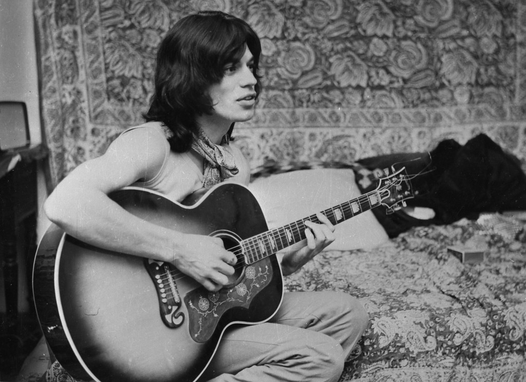 """. Mick Jagger, lead singer of the British rock band \""""The Rolling Stones\"""", is pictured playing his guitar in his dressing room in London between shooting scenes for the film \""""Performance\"""" on October 25, 1968. (AP Photo)"""