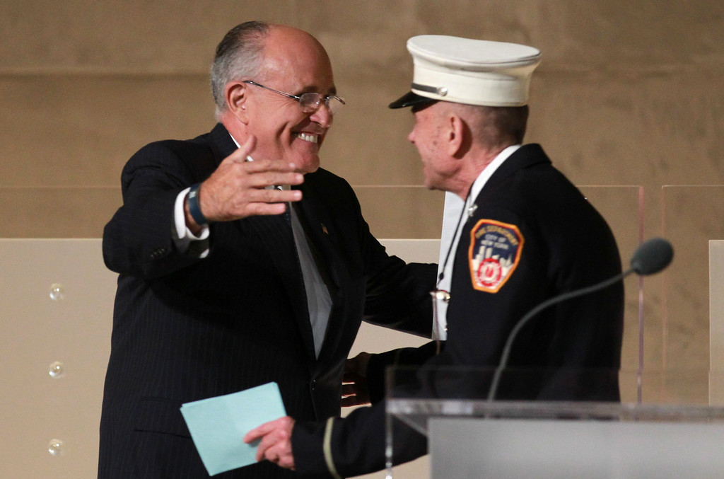 . Former New York Mayor Rudolph Giuliani hugs FDNY Lt Mickey Kross during the dedication ceremony at the National September 11 Memorial Museum May 15, 2014 in New York City. (Photo by John Munson-Pool/Getty Images)