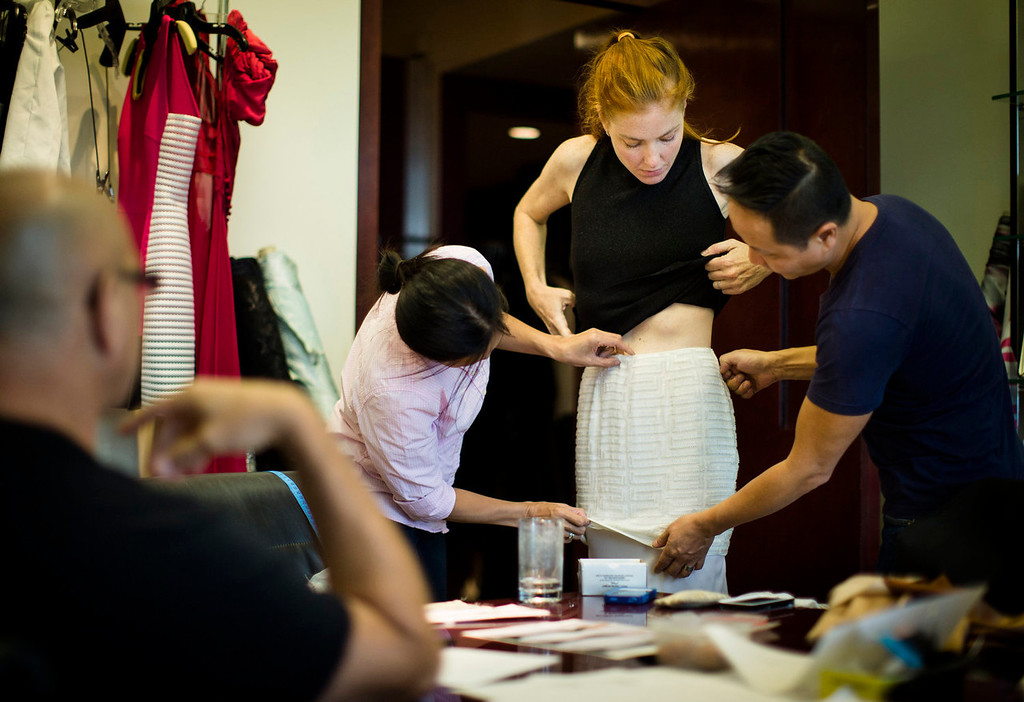 . Fashion designer Carmen Marc Valvo, left, supervises, pattern maker Luz Pyne, center left, and creative director Il Park adjusting  a skirt on Valvo\'s  model Taylor Foster at Valvo\'s New York studio. Valvo will show his Spring 2014 collection on Sept. 6 at Lincoln Center in New York. (AP Photo/John Minchillo)