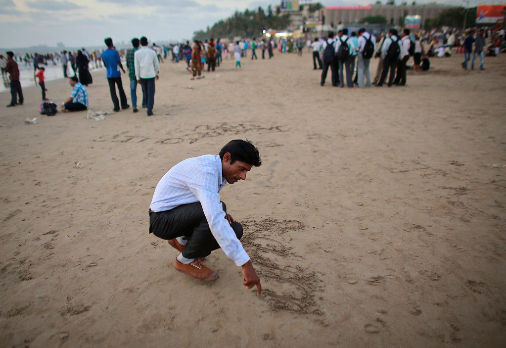 ". Ram Pratap Verma, a 32-year-old aspiring Bollywood film actor, writes his name on the sand at a beach in Mumbai April 17, 2013. Bollywood is an addiction for many; an addiction that attracts thousands of aspiring stars to the city of Mumbai. Ram Pratap Verma made the journey from his small village eight years ago, and despite carrying his whole ""home\"" inside his bag, he is determined not to give up on his ambitions. He endeavours to watch at least one film a week at a cinema, where the silver screen keeps his dreams alive. Picture taken April 17, 2013. REUTERS/Danish Siddiqui"