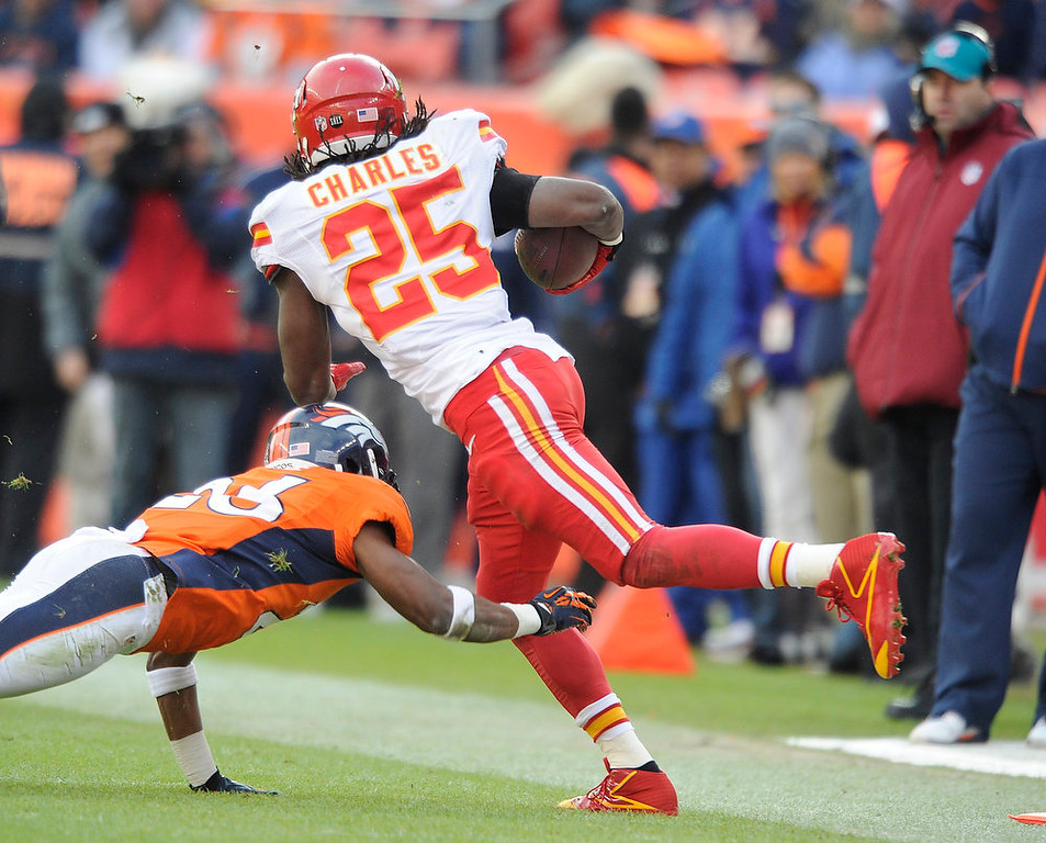 . Kansas City Chiefs running back Jamaal Charles (25) is tied up by Denver Broncos free safety Rahim Moore (26) as the Denver Broncos took on the Kansas City Chiefs at Sports Authority Field at Mile High in Denver, Colorado on December 30, 2012. Tim Rasmussen, The Denver Post