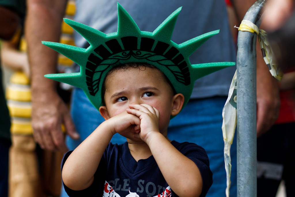 . A child attends a ceremony to reopen the Statue of Liberty and Liberty Island to the public in New York July 4, 2013. Under steamy summer skies, tourists in New York flocked to ferries headed for the Statue of Liberty, re-opening with an Independence Day ceremony after closing in October as Superstorm Sandy approached. REUTERS/Eduardo Munoz