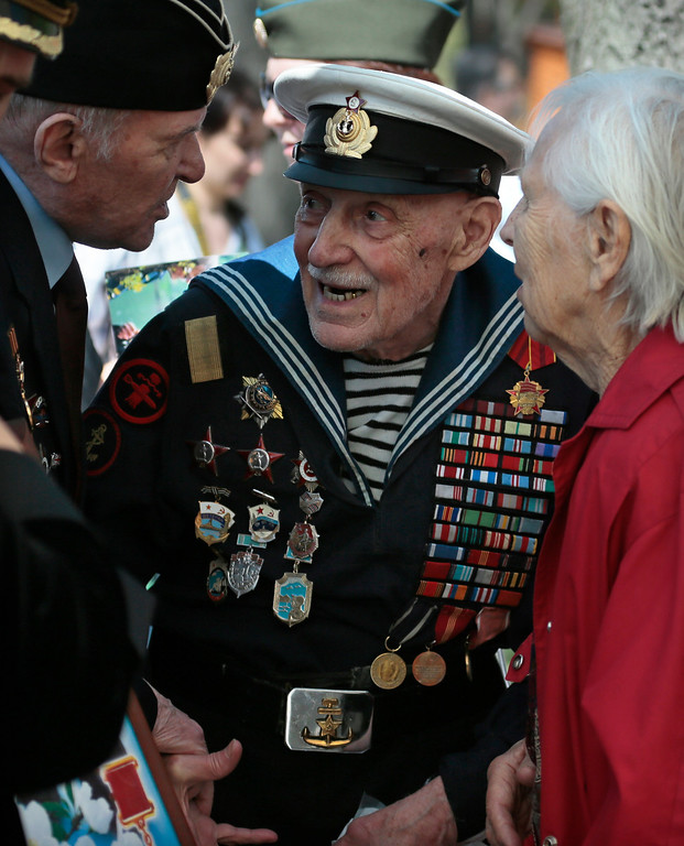 . WW II veteran Mikhail Podbursky 97, speaks with his friends as they celebrate Victory day in Moscow\'s Gorky park, Russia, Thursday, May 9, 2013. It is Russia\'s most important secular holiday, honoring the huge military and civilian losses of World War II and showing off the country\'s modern arsenal. (AP Photo/Mikhail Metzel)