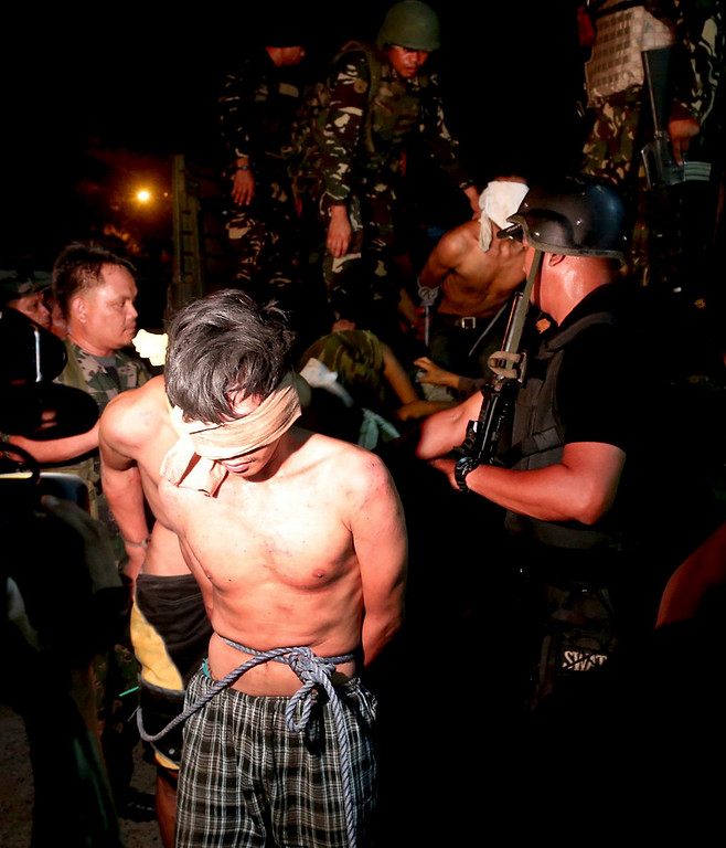 . In this photo taken Thursday Sept. 26, 2013, suspected Muslim rebels whom the military said were either captured or surrendered, arrive at a police station for processing in Zamboanga city, southern Philippines. The deadly three-week standoff between government troops and Muslim rebels, who taken nearly 200 people hostages has ended with all of the captives safe, officials announced Saturday Sept. 28, 2013. Defense Secretary Voltaire Gazmin said only a handful of Moro National Liberation Front rebels remained in hiding and were being hunted by troops in the coastal outskirts of Zamboanga city, adding authorities were trying to determine if rebel commander Habier Malik, who led the Sept. 9 siege, was dead. More than 200 people were killed in the clashes, including 183 rebels and 23 soldiers and police, in one of the bloodiest and longest-running attacks by a Muslim group in the south, scene of decades-long Muslim rebellion for self-rule in the largely Roman Catholic country. (AP Photo)