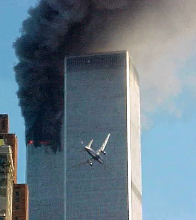 . In this Sept. 11, 2001 file photo, a jet airliner is lined up on one of the World Trade Center towers in New York. (AP Photo/Carmen Taylor, File)