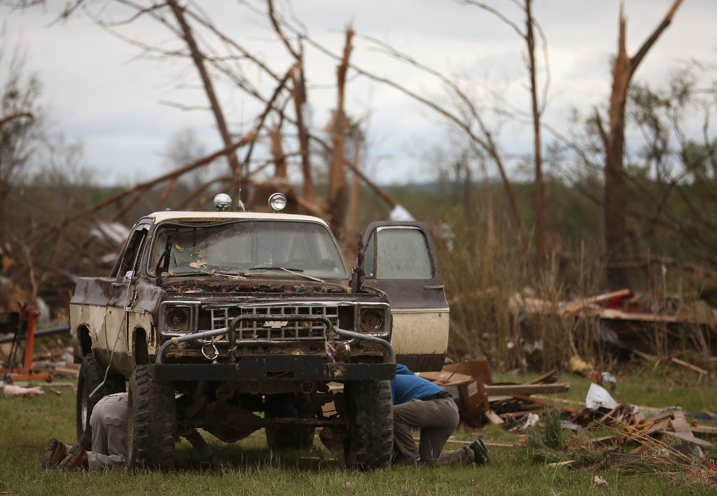 . Two men work on an old Chevy truck that was damaged by a tornado, April 30, 2014 in Mayflower, Arkansas. Deadly tornadoes ripped through the region starting on April 27 leaving more than two dozen dead. The storm system has also brought severe flooding to Florida\'s Panhandle.  (Photo by Mark Wilson/Getty Images)