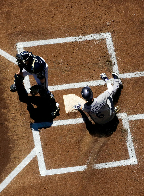 . Colorado Rockies\' Corey Dickerson slides home safely past Milwaukee Brewers catcher Jonathan Lucroy during the first inning of a baseball game Sunday, June 29, 2014, in Milwaukee. Dickerson scored from second on a hit by Wilin Rosario. (AP Photo/Morry Gash)
