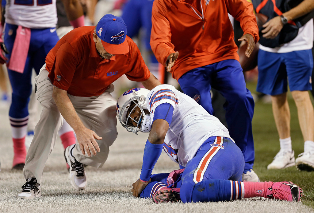 . A trainer rushes to help Buffalo Bills quarterback EJ Manuel after he was injured on a third-quarter run against the Cleveland Browns in the third quarter of an NFL football game Thursday, Oct. 3, 2013, in Cleveland. (AP Photo/Tony Dejak)
