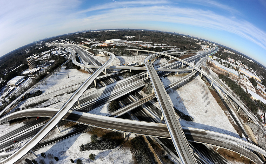 ". In this photo taken with a fisheye lens over the city\'s perimeter highway known as ""Spaghetti Junction,\"" the ice-covered interstate system shows the remnants of a winter snow storm that slammed the city with over 2 inches of snow that turned highways into parking lots when motorists abandoned their vehicles creating massive traffic jams lasting through, Wednesday, Jan. 29, 2014, in Atlanta. While such amounts of accumulation barely quality as a storm in the north, it was enough to paralyze the Deep South. (AP Photo/David Tulis)"