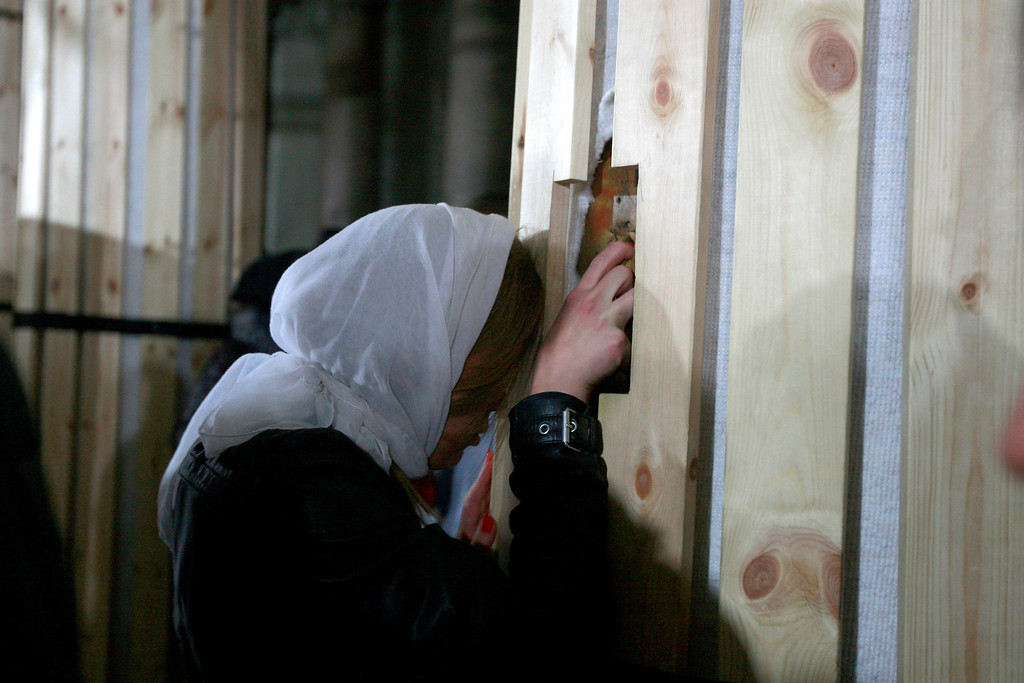 . A Christian pilgrim touches a column inside the Church of the Nativity, traditionally believed by Christians to be the birthplace of Jesus Christ, in the West Bank town of Bethlehem on Christmas Eve, Tuesday, Dec. 24, 2013. (AP Photo/Majdi Mohammed)