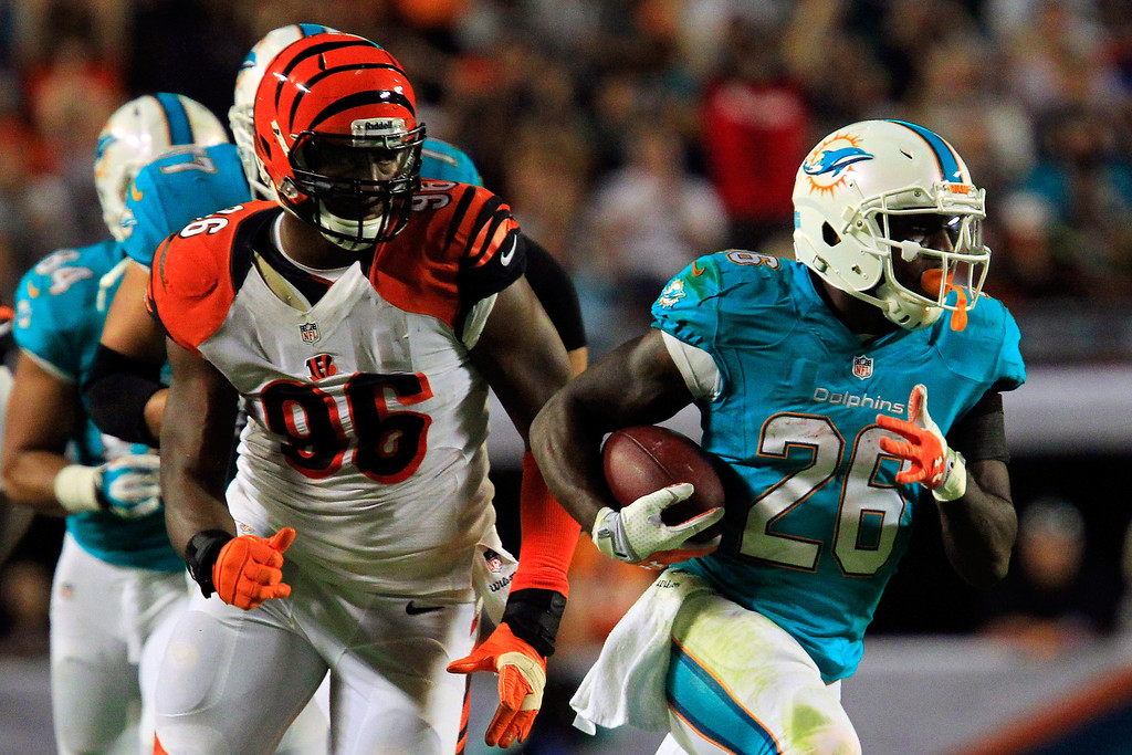 . MIAMI GARDENS, FL - OCTOBER 31: (R) Lamar Miller #26 of the Miami Dolphins runs with the ball under pressure from Carlos Dunlap #96 of the Cincinnati Bengals at Sun Life Stadium on October 31, 2013 in Miami Gardens, Florida. (Photo by Chris Trotman/Getty Images)