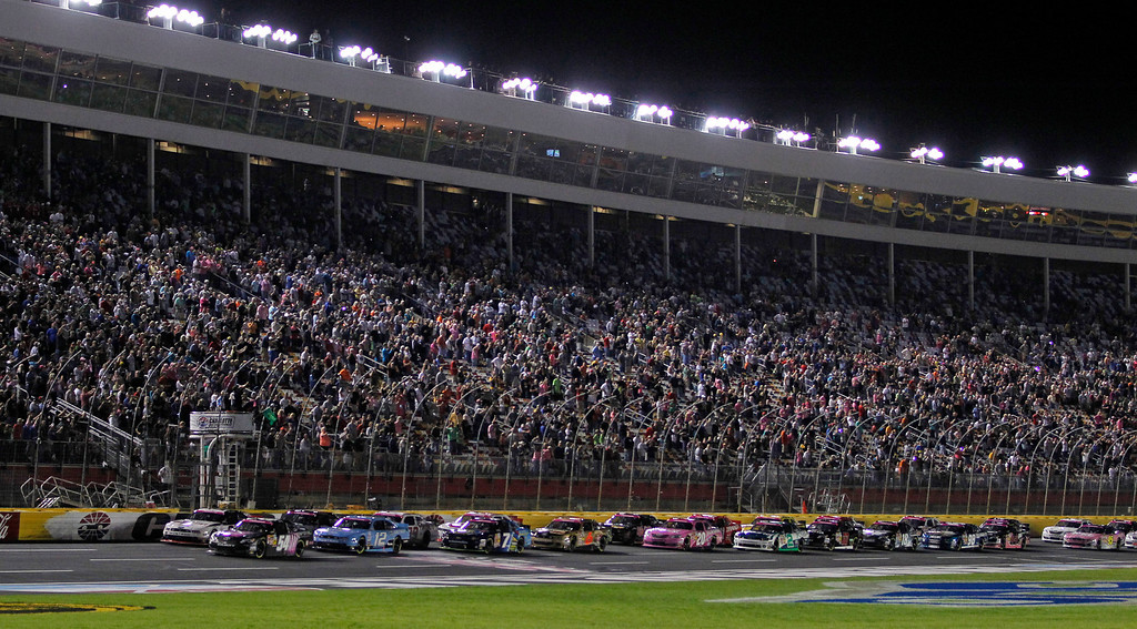 . Kyle Busch (54) leads the field at the start of a NASCAR Nationwide series auto race at Charlotte Motor Speedway in Concord, N.C., Friday, Oct. 11, 2013. (AP Photo/Terry Renna)