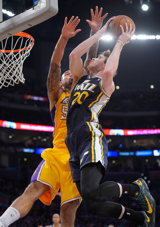 . Utah Jazz guard Gordon Hayward, right, goes up for a shot as Los Angeles Lakers center Robert Sacre defends during the first half of an NBA basketball game, Friday, Jan. 3, 2014, in Los Angeles. (AP Photo/Mark J. Terrill)