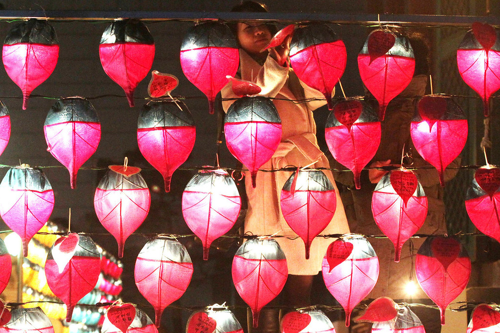 . A Buddhist woman attaches her name card on a lantern ahead of the new year at Chogye Buddhist temple in Seoul, South Korea, Tuesday, Dec. 31, 2013.  (AP Photo/Ahn Young-joon)
