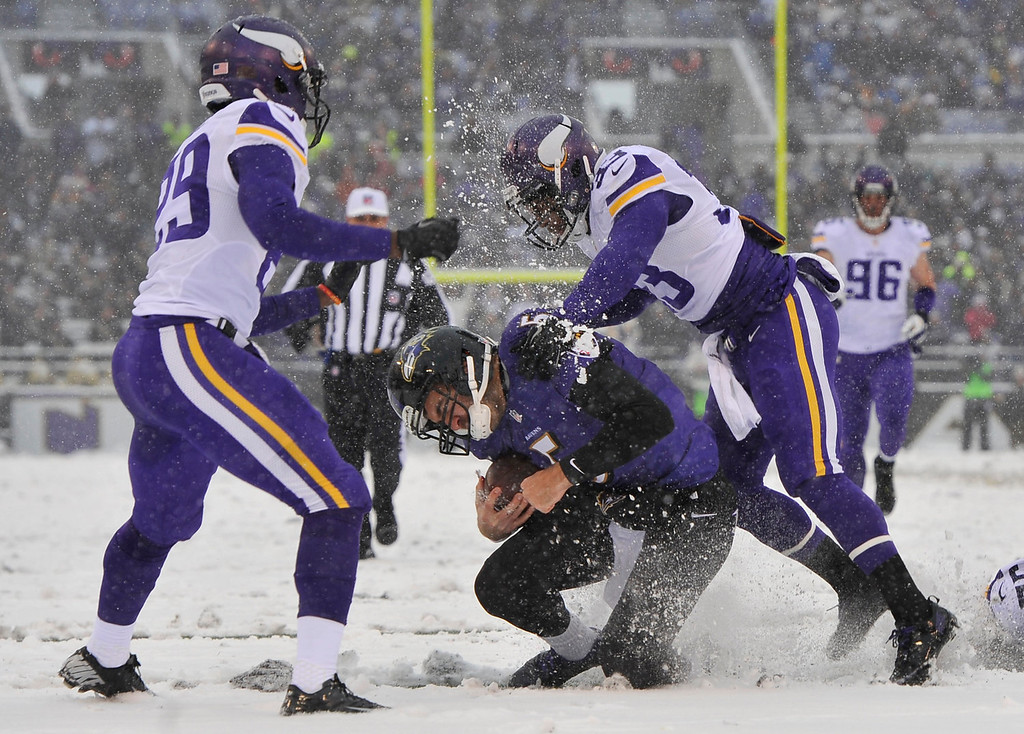 . Baltimore Ravens quarterback Joe Flacco, center, is tackled by Minnesota Vikings strong safety Jamarca Sanford, right, as cornerback Xavier Rhodes, left, looks on in the first half of an NFL football game, Sunday, Dec. 8, 2013, in Baltimore. (AP Photo/Gail Burton)