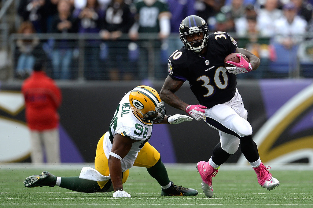 . Bernard Pierce #30 of the Baltimore Ravens avoids the tackle of Mike Neal #96 of the Green Bay Packers in the first half during a game at M&T Bank Stadium on October 13, 2013 in Baltimore, Maryland.  (Photo by Patrick McDermott/Getty Images)