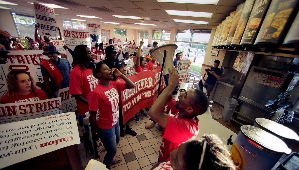 """. Protesters gather inside a Taco Bell restaurant in Kansas City, Mo. on Thursday, Sept. 4, 2014, as part of the \""""Fight for $15\"""" campaign, a national protest to push fast-food chains to pay their employees at least $15 an hour. The movement, which is backed financially by the Service Employees International Union and others, has gained national attention at a time when the wage gap between the poor and the rich has become a hot political issue.  (AP Photo/Charlie Riedel)"""
