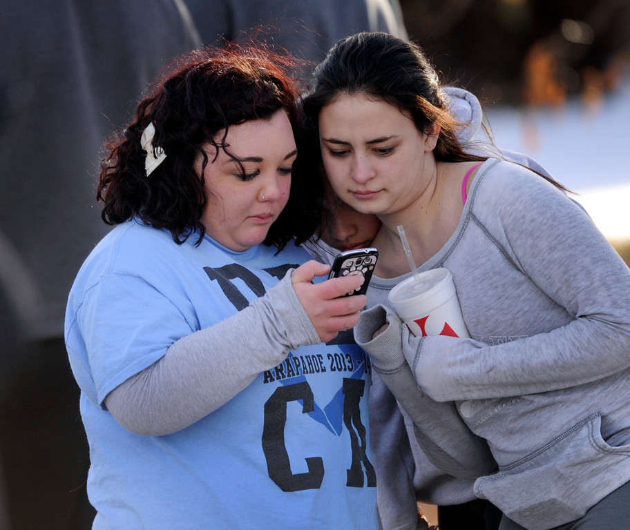 . CENTENNIAL, CO. - DECEMBER 13: Arapahoe High School senior Alex Boyle, left, shared a view of her phone with a friend outside Arapahoe High School Friday afternoon, December 13, 2013. A shooting inside the school sent hundreds of students rushing for safety. Photo By Karl Gehring/The Denver Post