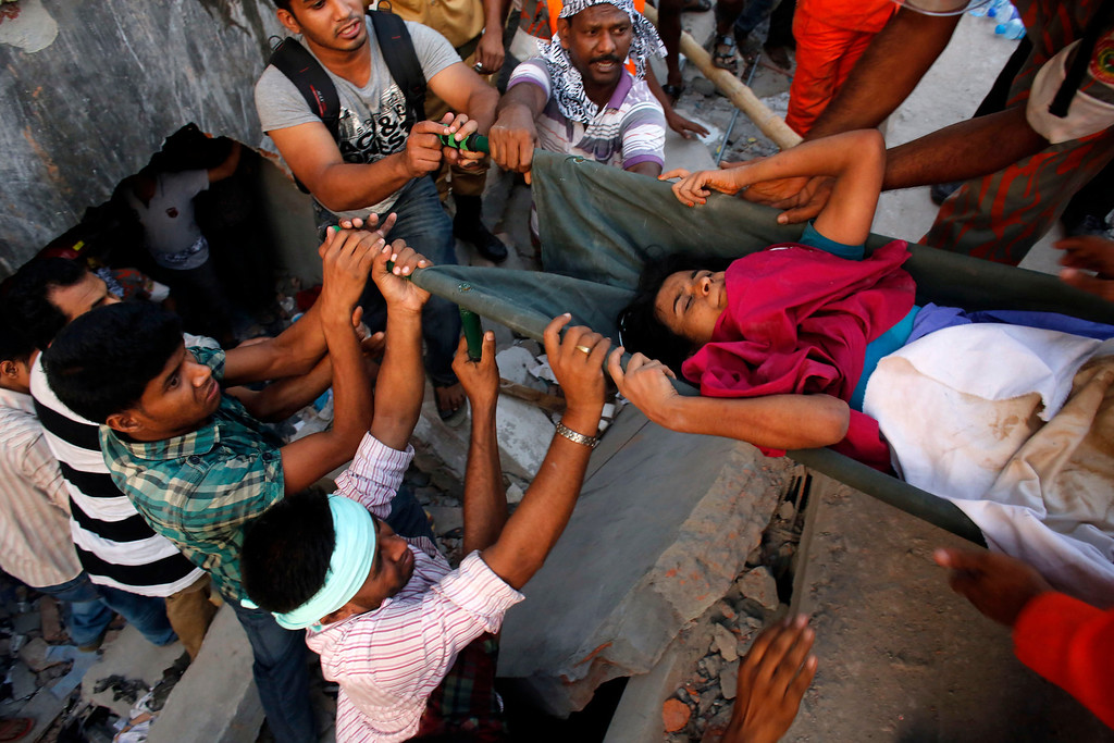 . Rescue workers try to rescue the trapped garment workers in the Rana Plaza building which collapsed in Savar, 30 km (19 miles) outside Dhaka April 24, 2013. A block housing garment factories and shops collapsed in Bangladesh on Wednesday, killing nearly 100 people and injuring more than a thousand, officials said.REUTERS/Andrew Biraj