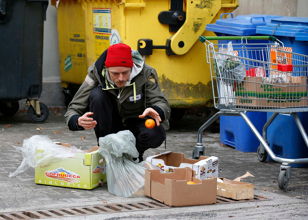 . Raphael Fellmer, a supporter of the foodsharing movement sorts out food from waste bins at the parking lot of an organic supermarket in Berlin, January 31, 2013. Foodsharing is a German internet based platform where individuals, retailers or producers have the possibility of offering surplus food to consumers for free.   REUTERS/Fabrizio Bensch