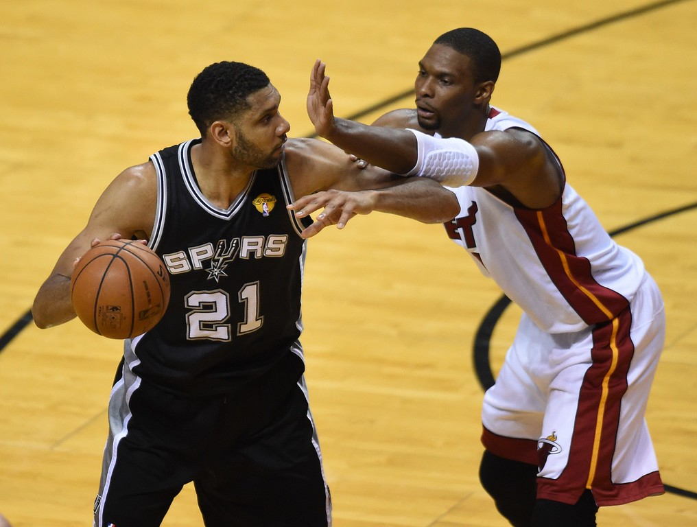 . Miami Heat\'s  Chris Bosh (R) defends against Tim Duncan of the San Antonio Spurs (L) during Game 4 of the 2014 NBA Finals on June 12, 2014  at the American Airlines Arena in Miami, Florida.  TIMOTHY A. CLARY/AFP/Getty Images