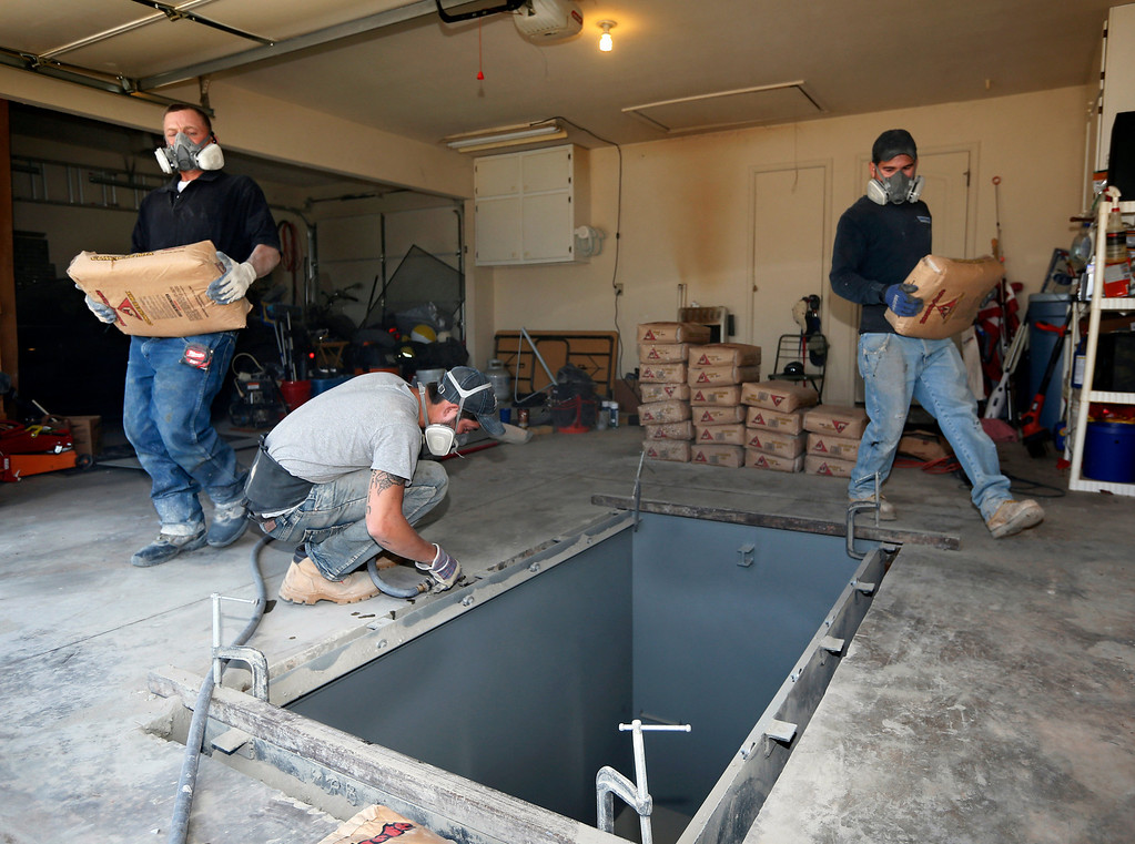 . In this Thursday, May 1, 2014 photo, Jim Hohnsbehn, left, Dustin Wagner, center, and Jacob Ortiz, of Thunderground Storm Shelters, prepare to fill in the sides of a hole with concrete during the installation of a storm shelter in the garage of a residence in Oklahoma City. (AP Photo/Sue Ogrocki)