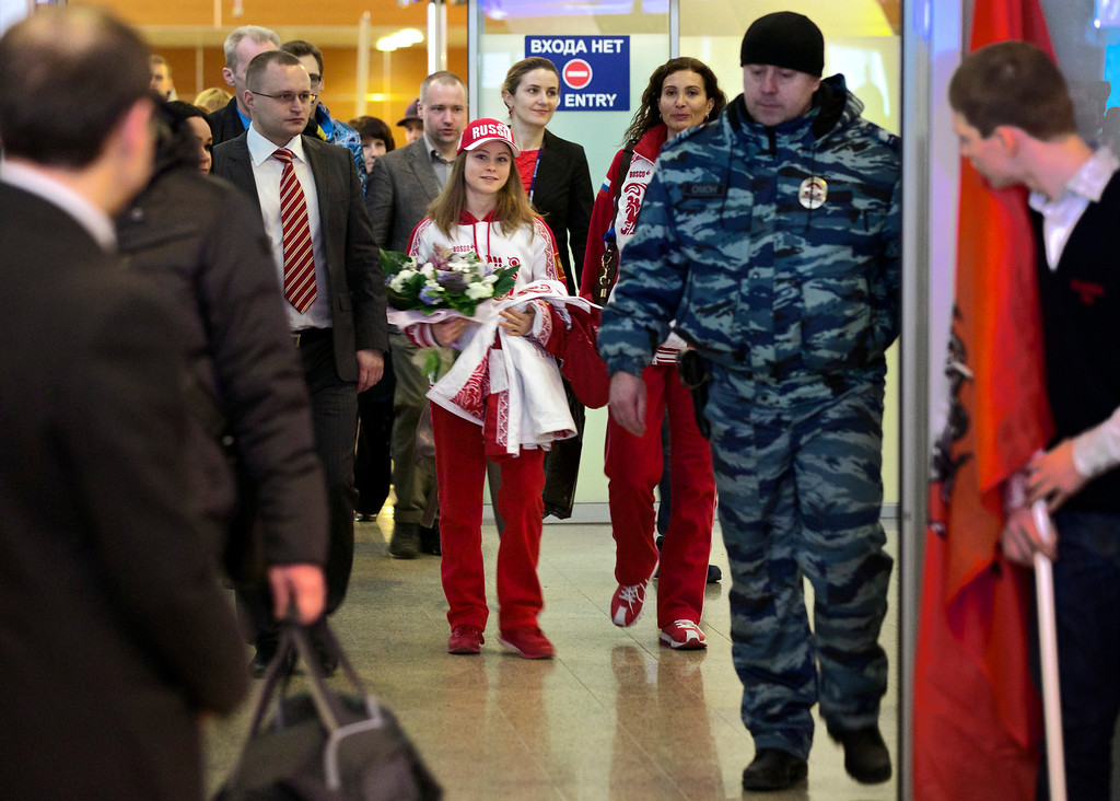 Description of . Russian Julia Lipnitskaia, center, walks through a corridor surrounded by police officers in the Sheremetyevo airport, outside Moscow, Russia, Tuesday, Feb. 11, 2014.Russian figure-skating 15-year-old phenomenon Lipnitskaia has returned to Moscow to train for what she hopes will be another gold medal. She already has one in the team skating and says it is ìvery heavy but beautiful.î Next on her agenda is the womenís competition, which begins Feb. 19 in Sochi. Until then, Lipnitskaia plans to train in Moscow. (AP Photo/Alexander Zemlianichenko)