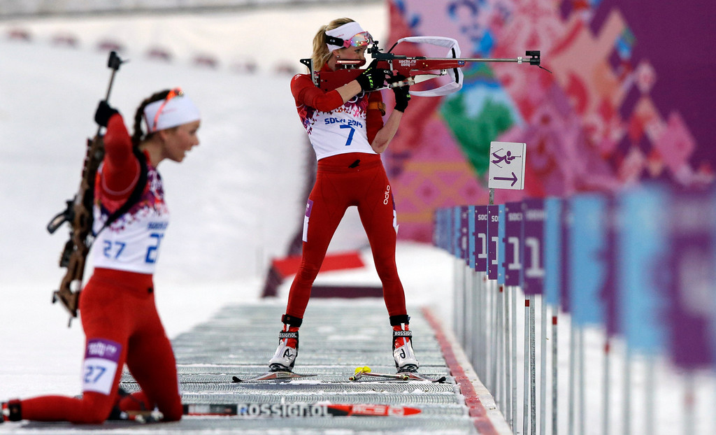 . Switzerland\'s Elisa Gasparin, top, shoots as her sister Selina Gasparin gets ready to shoot, during the women\'s biathlon 15k individual race, at the 2014 Winter Olympics, Friday, Feb. 14, 2014, in Krasnaya Polyana, Russia. (AP Photo/Lee Jin-man)