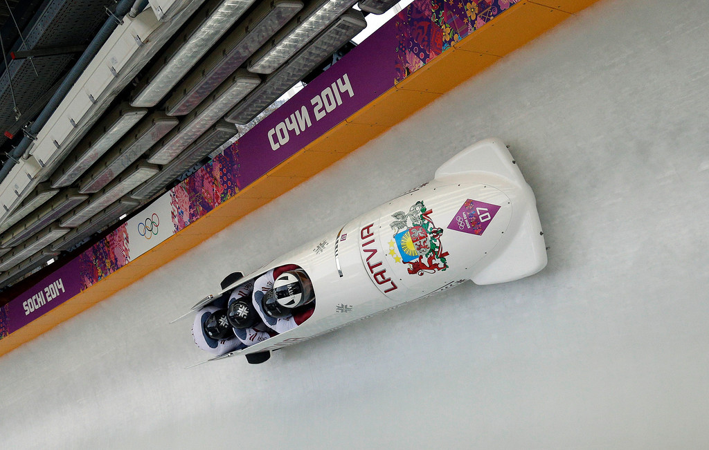 . The team from Latvia LAT-1, with Oskars Melbardis, Daumants Dreiskens, Arvis Vilkaste and Janis Strenga, take a curve during the men\'s four-man bobsled competition final at the 2014 Winter Olympics, Sunday, Feb. 23, 2014, in Krasnaya Polyana, Russia. (AP Photo/Michael Sohn)