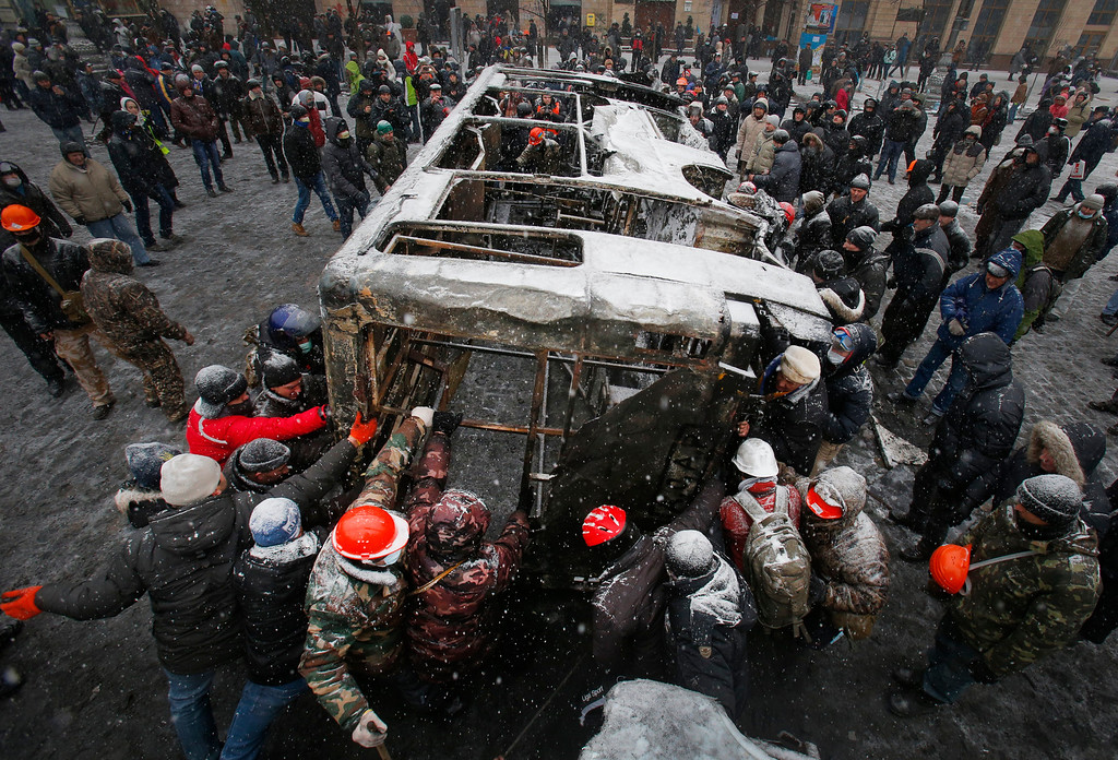 . Opposition supporters move a bus  torched by protesters overnight to build a new barricade in central Kiev, Ukraine, Tuesday, Jan. 21, 2014. Opposition leader Vitali Klitschko headed for talks with the Ukrainian president on Tuesday after yet another night of violent street clashes between anti-government protesters and police. (AP Photo/Sergei Grits)