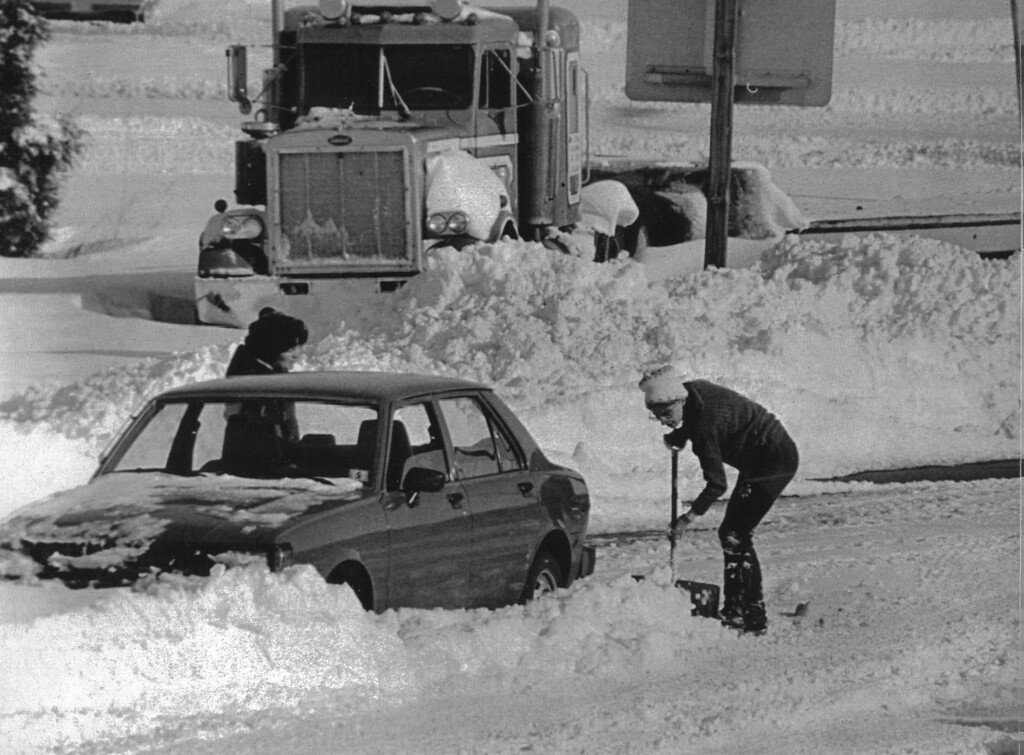 . Unidentified woman digs out her car on one of Denver main streets December 25, 1982 after a blizzard dropped three feet of snow on the area Christmas Day. A abandoned jack knifed semi trailer is snowed in. Credit: UPI . Denver Post Library Archive