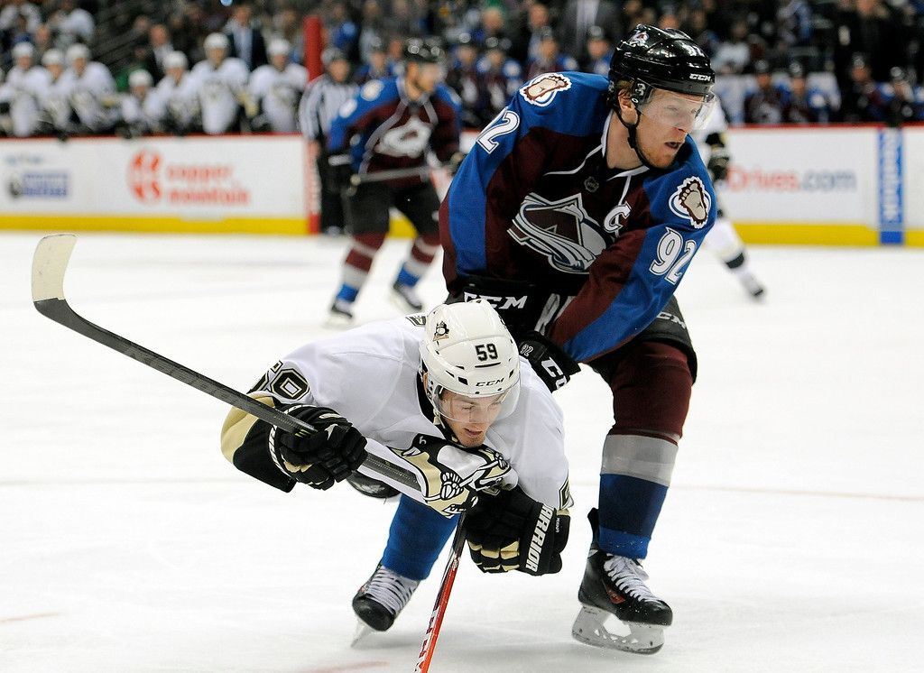 . Colorado Avalanche left wing Gabriel Landeskog, top, of Sweden, trips Pittsburgh Penguins right wing Jayson Megna during the third period of an NHL hockey game Sunday, April 6, 2014, in Denver. The Penguins won in a shootout, 3-2. (AP Photo/Chris Schneider)