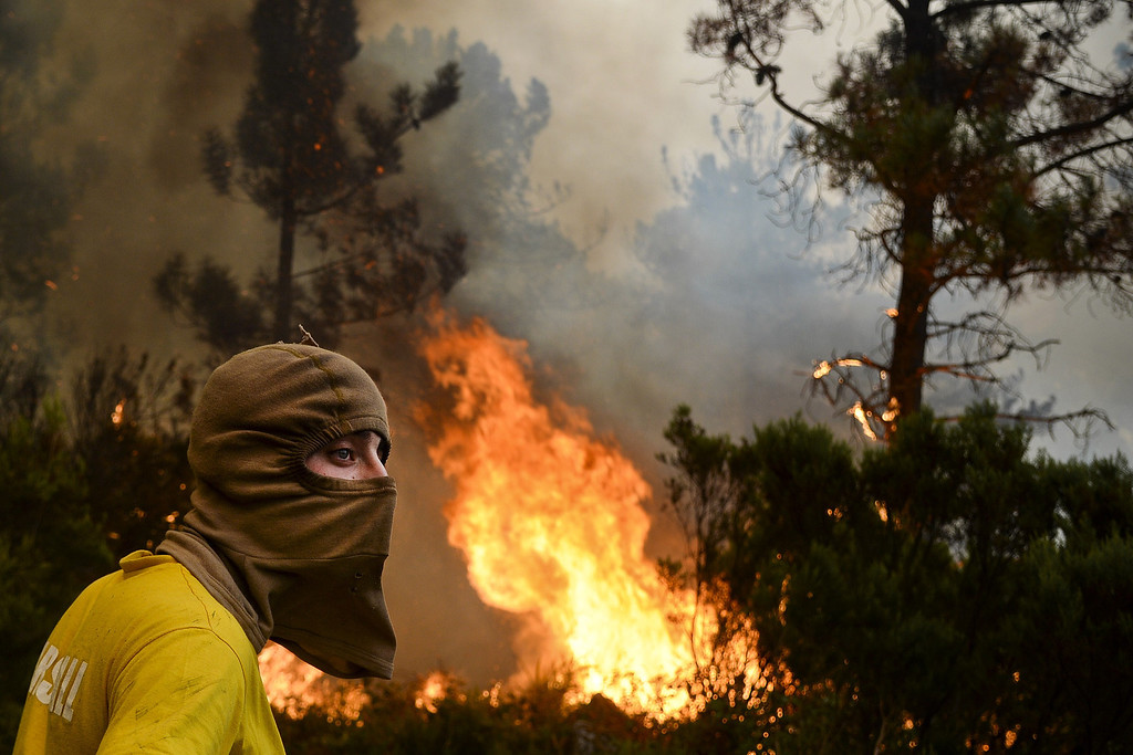 . A local wearing a balaclava stands near a wildfire in Caramulo, central Portugal on August 29, 2013.    AFP PHOTO / PATRICIA DE MELO  MOREIRA/AFP/Getty Images