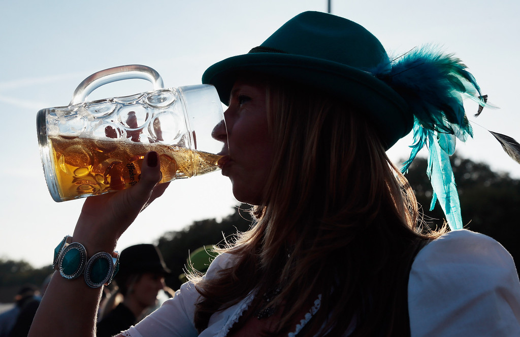 . A woman drinks beer outside a beer tent during day 1 of the Oktoberfest 2013 beer festival at Theresienwiese on September 21, 2013 in Munich, Germany. The Munich Oktoberfest, which this year will run from September 21 through October 6, is the world\'s largest beer fest and draws millions of visitors.  (Photo by Johannes Simon/Getty Images)