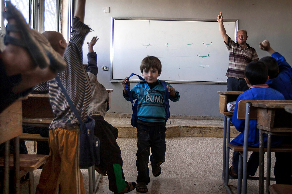 . In this Thursday, Sept. 26, 2013 photo, a Syrian teacher leads a class at the public school in Madaya village as classes begin in the Idlib province countryside of Syria. Millions of Syrian children most of them in government-controlled areas have returned to school in the past two weeks, despite the conflict that according to UNICEF has left 4,000 Syrian schools or one in five damaged, destroyed or sheltering displaced families. (AP Photo)