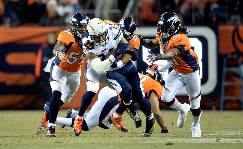 . San Diego Chargers running back Ryan Mathews (24) gets taken down by Denver Broncos strong safety Mike Adams (20) in the first quarter.  The Denver Broncos vs. the San Diego Chargers at Sports Authority Field at Mile High in Denver on December 12, 2013. (Photo by Hyoung Chang/The Denver Post)