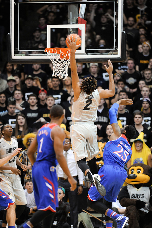 . Colorado University forward, Xavier Johnson, slam dunks against Kansas forward, Tarik Black, right, in the first half of play at the Coors Events Center in Boulder Colorado Saturday afternoon, December 07, 2013. (Photo By Andy Cross/The Denver Post)