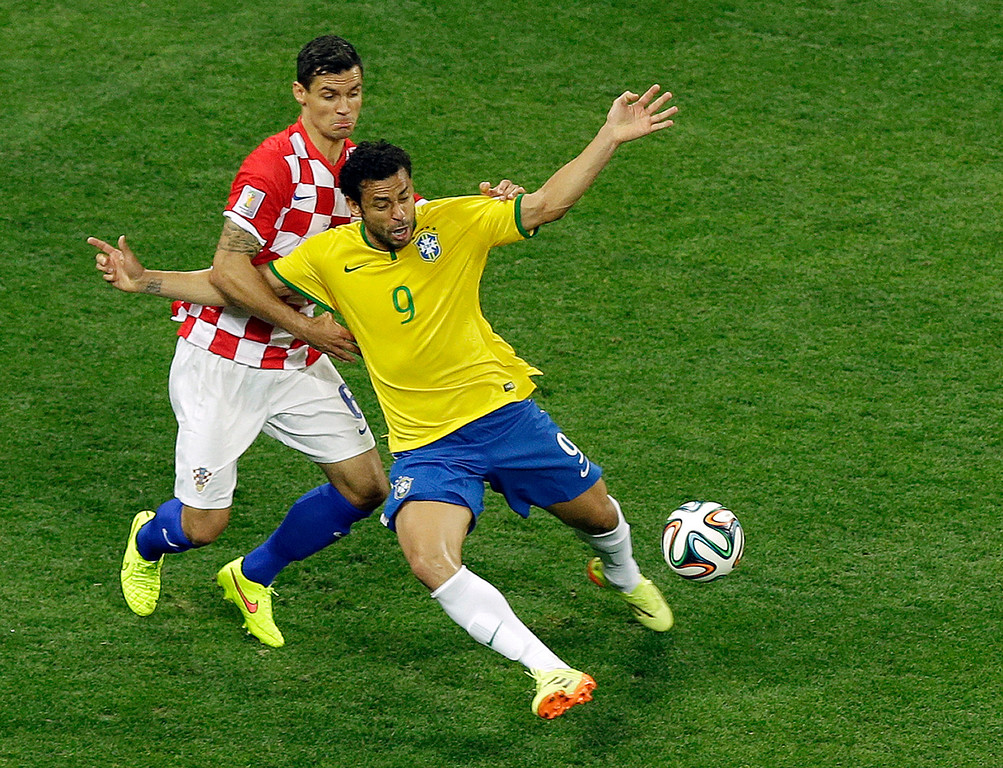 . Brazil\'s Fred, right, falls after making contact with Croatia\'s Dejan Lovren during the group A World Cup soccer match between Brazil and Croatia, the opening game of the tournament, in the Itaquerao Stadium in Sao Paulo, Brazil, Thursday, June 12, 2014. (AP Photo/Thanassis Stavrakis)