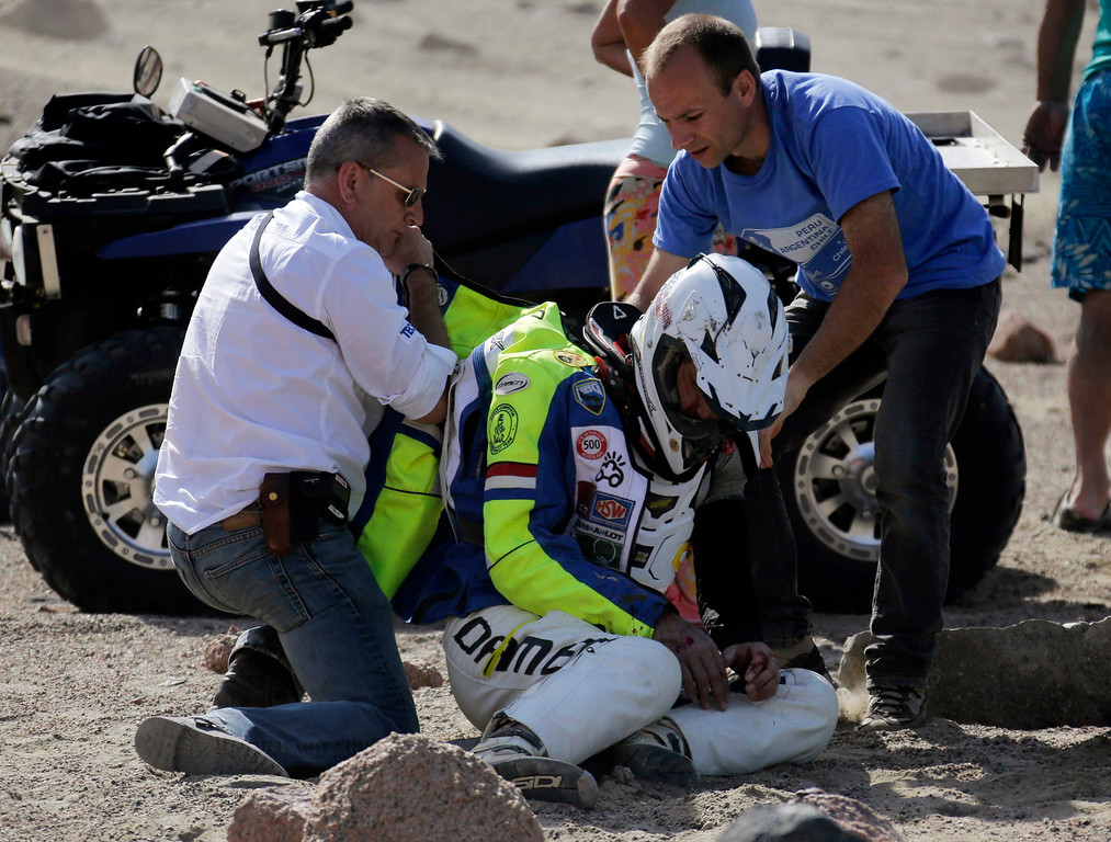 . Etienne Lavigne (L), Director of the Dakar Rally 2013, and a doctor attend to Netherland\'s Henno Van Bergeijk after he crashed on his Husaberg during the 3rd stage of the rally from Pisco to Nazca January 7, 2013.  REUTERS/Jacky Naegelen