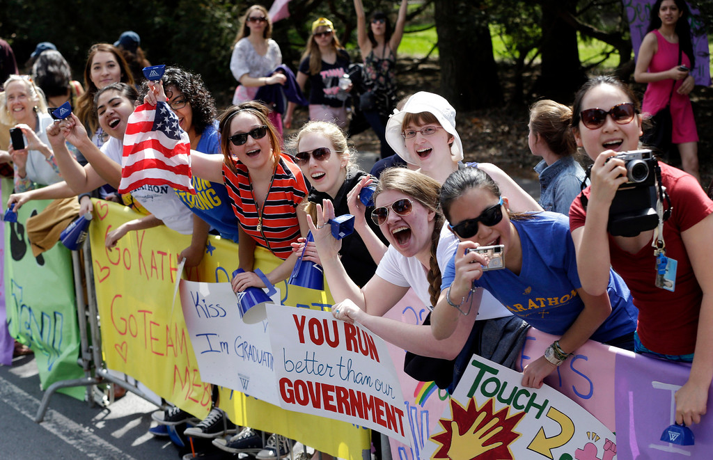 . Women display placards and cheer near Wellesley College along the route of the 118th Boston Marathon, Monday, April 21, 2014, in Wellesley, Mass. (AP Photo/Steven Senne)