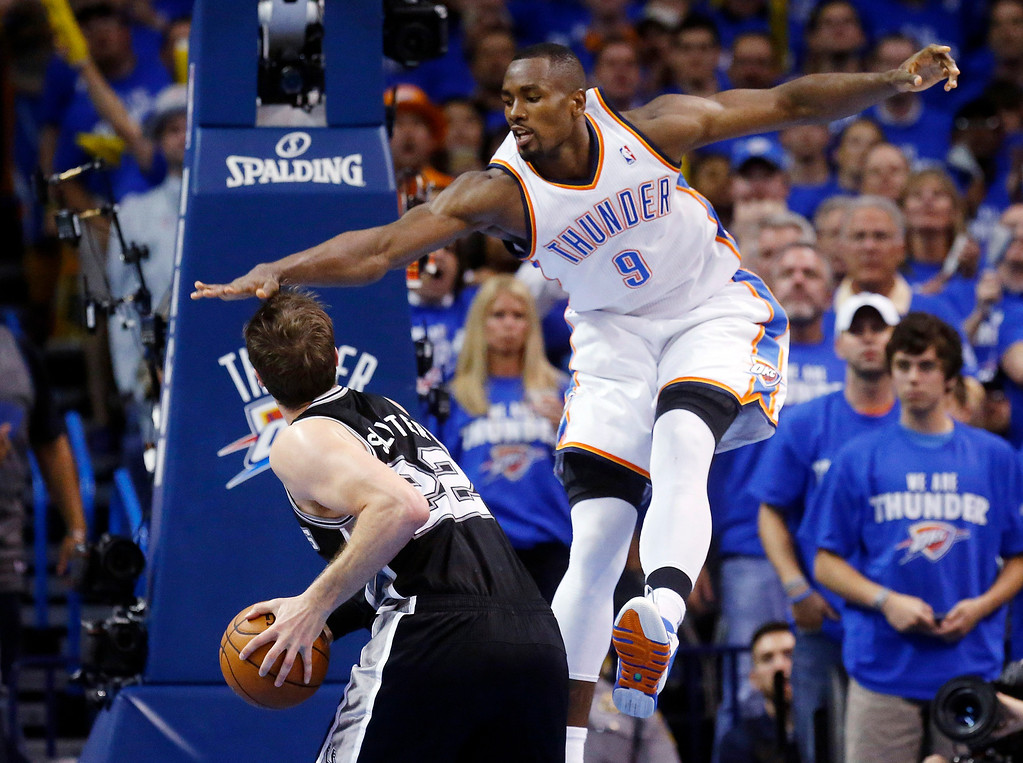 . Oklahoma City Thunder forward Serge Ibaka (9) gets up to block a shot by San Antonio Spurs center Tiago Splitter (22) in the second quarter of Game 4 of the Western Conference finals NBA basketball playoff series in Oklahoma City, Tuesday, May 27, 2014. (AP Photo/Sue Ogrocki)
