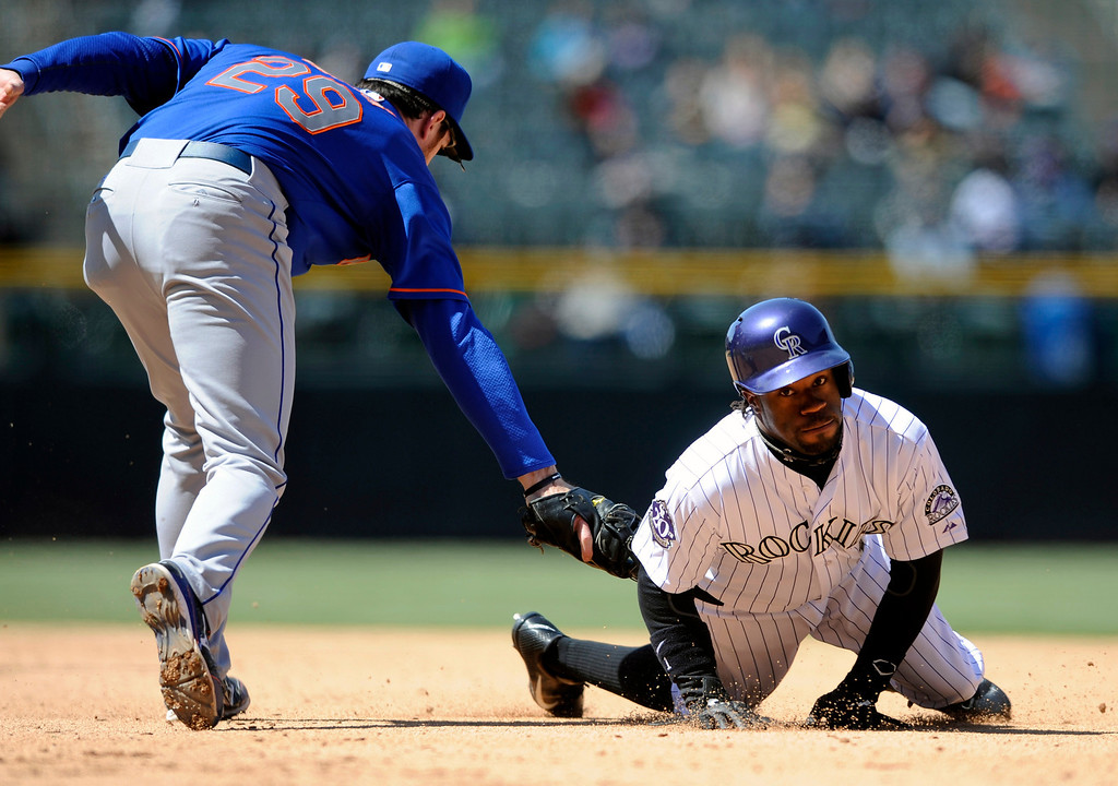 . Colorado Rockies\' Eric Young Jr. (1) is caught between the base by New York Mets first baseman Ike Davis (29) during the fifth inning of a baseball game on Thursday, April 18, 2013, in Denver. (AP Photo/Jack Dempsey)