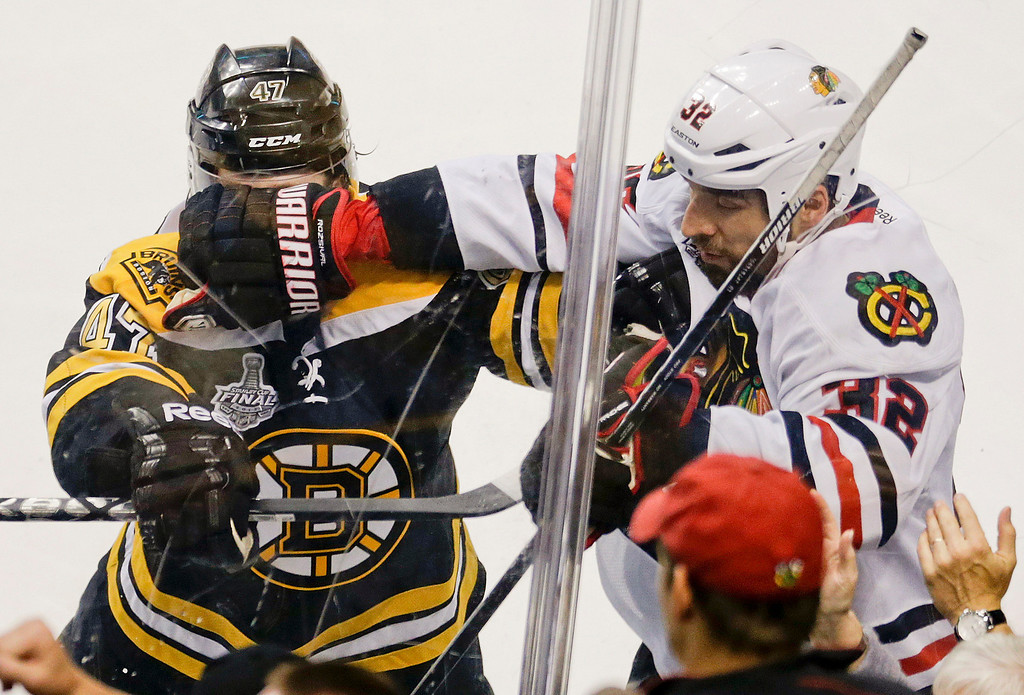 . Boston Bruins defenseman Torey Krug (47) and Chicago Blackhawks defenseman Michal Rozsival (32), of the Czech Republic, mix it up during the first period in Game 4 of the NHL hockey Stanley Cup Finals, Wednesday, June 19, 2013, in Boston. (AP Photo/Charles Krupa)