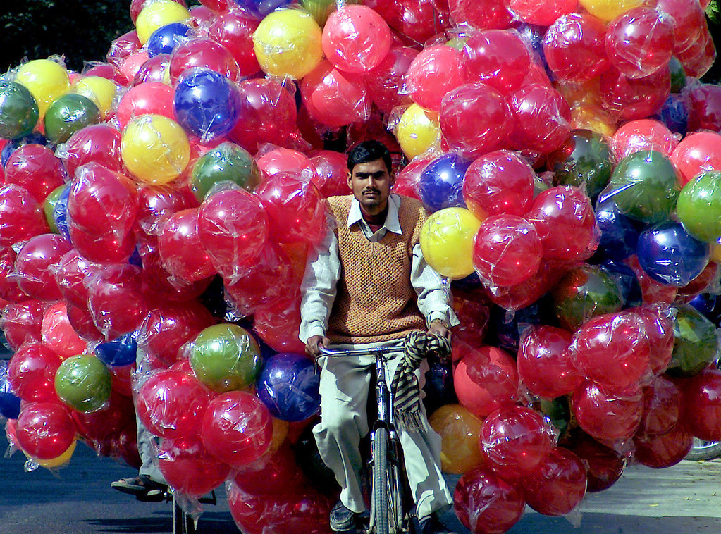 . An Indian man carries plastic balls on his bicycle in the northern Indian city Lucknow February 16, 2006. REUTERS/Pawan Kumar